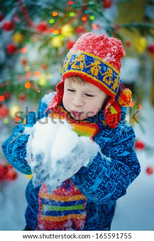 A boy in a red patterned knitted cap with ear-flaps and with a bright scarf playing with snow near the decorated Christmas tree on a frosty winter day outdoor