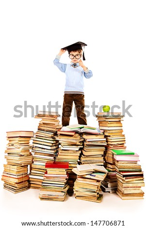 A boy in the academic hat standing on a pile of books. Education. Isolated over white.