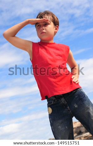 A boy in the summer sunshine with hand to forehead, searching and looking out to the distance - stock photo