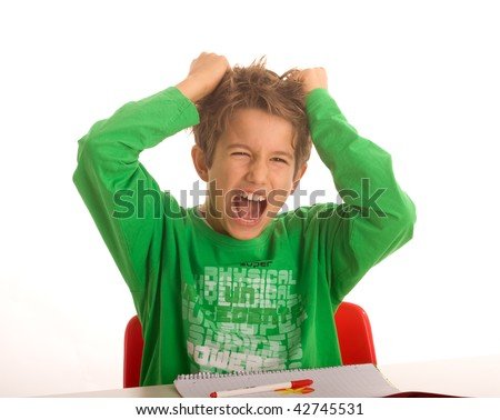 A boy is angry while doing his homework - stock photo