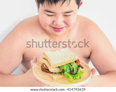 A boy is happily looking at sandwich. Photo is focused at sandwich. - stock photo