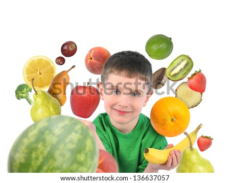 A boy is holding a banana and apple with a variety of fruit food around the child. There is a white isolated background for a diet concept.
