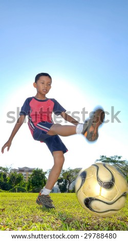 A boy is kicking a ball during evening - stock photo