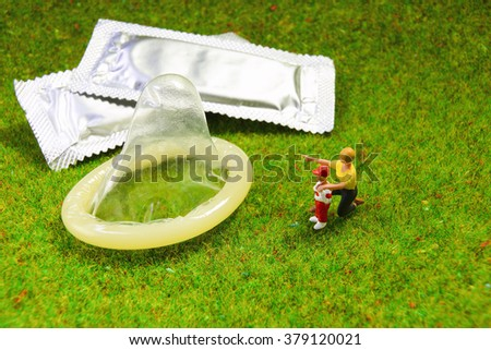 A boy is learning to use condom from his mother. Education concept - stock photo