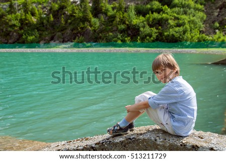 A boy is sitting at  lake in hot summer day