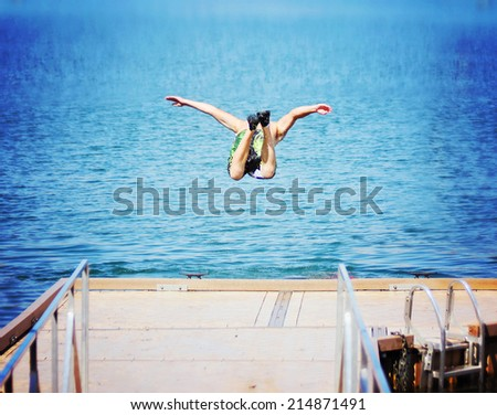 a boy jumping of an old dock into a pond  - stock photo