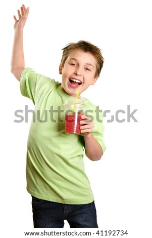 A boy jumps in delight.   He is holding a healthy fruit juice and smiling with glee. - stock photo
