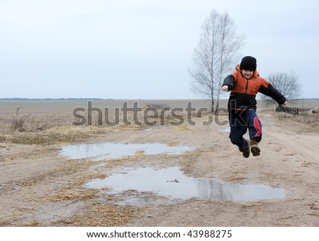 A boy jumps over a puddle on a rural road