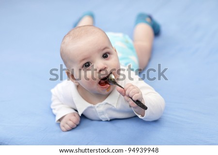 A boy licking spoon of iron syrup on a blue sheet - stock photo