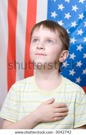 A boy listening national anthem on 4th of July - stock photo