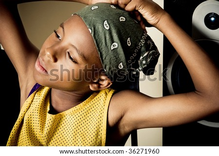 a boy listens to music from a speaker in the background - stock photo
