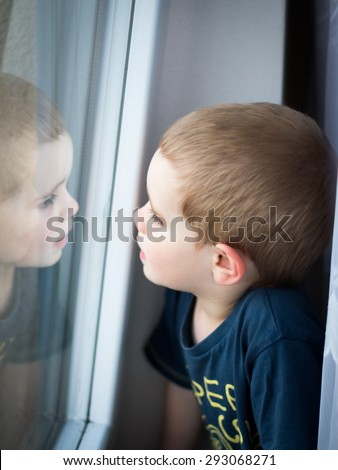 A boy looking out of the window - stock photo