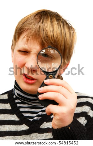 A boy looking through a magnifying glass on a white background - stock photo