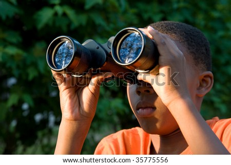 a boy looks for wildlife through binoculars - stock photo