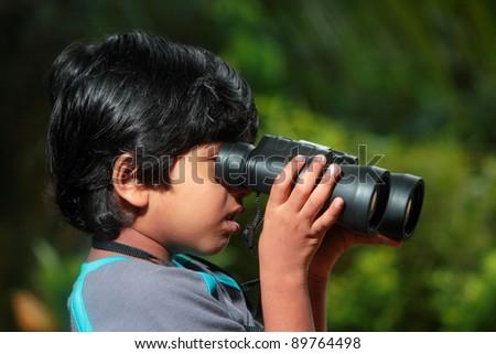 A boy looks through binoculars in outdoor - stock photo