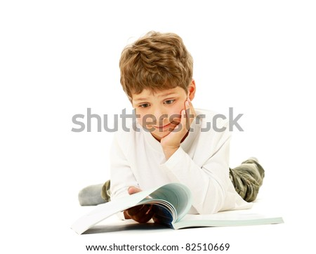 A boy lying on the floor and reading a book, isolated on white - stock photo