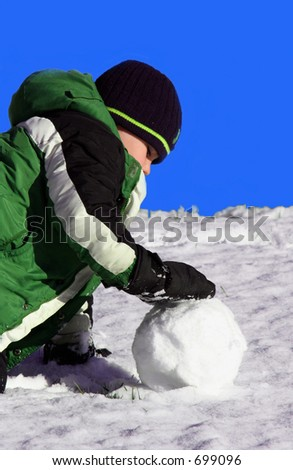 a boy making a snowball - stock photo