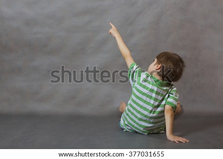 A boy of six years old shows at something being turned with his back. Gray background
