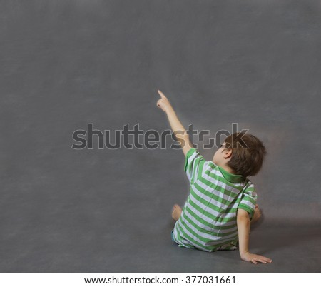 A boy of six years old shows at something being turned with his back. Gray background. Free space for a text.