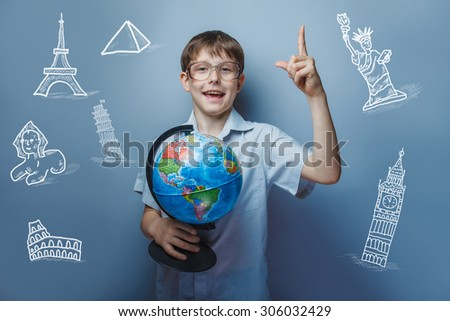 a boy of 10 years of European appearance with glasses holding a globe in hands  on a gray  background - stock photo