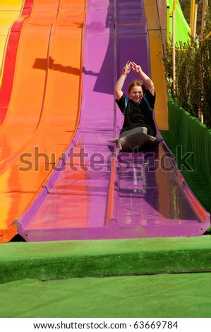 A boy on a giant carnival slide - stock photo