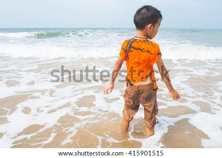 a boy on the beach with message in a bottle.  - stock photo