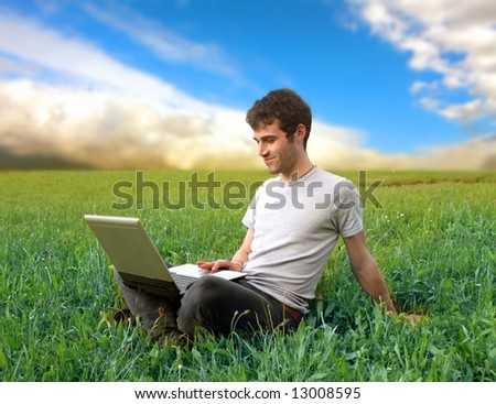 a boy on the grass field with a laptop