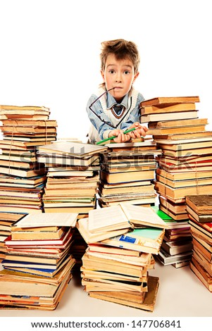 A boy peeking out from behind a heap of books. Education. Isolated over white.