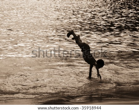 a boy performs cartwheels in the ocean - stock photo
