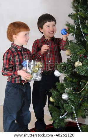 A boy places an ornament on a Christmas tree with the help of his brother - stock photo