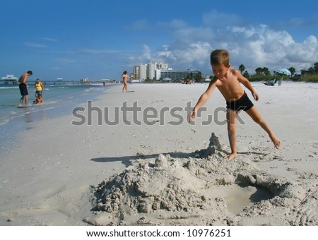 A boy playing in the sand on the beach - stock photo