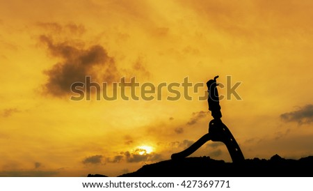 A boy playing on a the hill at sunset,silhouette concept. - stock photo