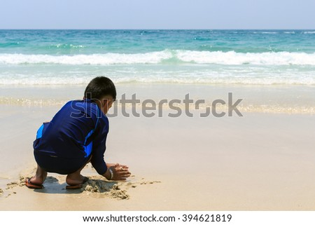 A boy playing on the beach sand