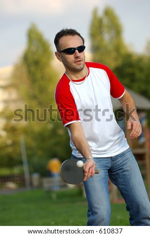 A boy playing ping-pong in a park