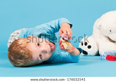 A boy playing with block while lying on the floor. - stock photo
