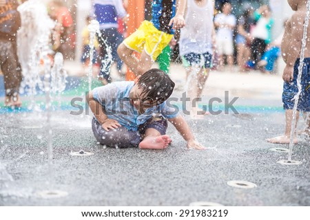 A boy playing with water in park fountain. Hot summer. Happy young boy has fun playing in water fountains - stock photo