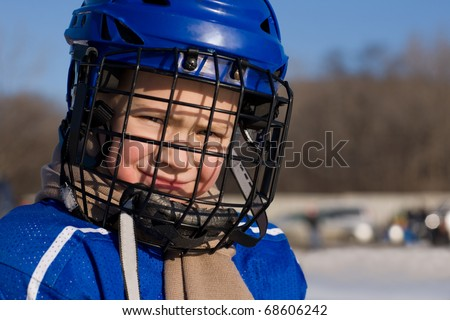 A boy plays hockey on the outdoor ice area. Boy seven years. - stock photo