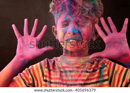 A boy plays Holi with colored powder exploding around his face in a dark background.Concept for Indian festival Holi - stock photo