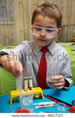 A boy plays in the academic chemist - stock photo