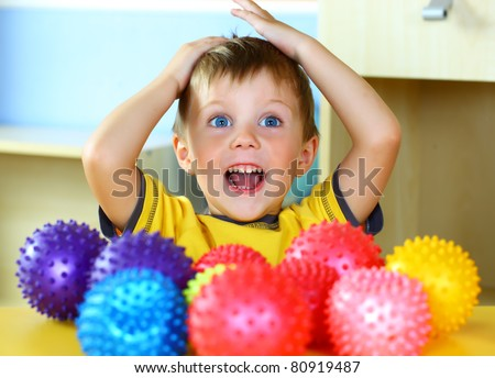 A boy plays with rubber colored balls - stock photo