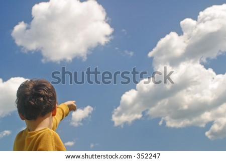 A boy pointing up at the clouds - stock photo