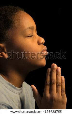 A boy prays to God. - stock photo