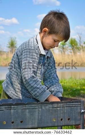 A boy prepares to picnic BBQ - stock photo