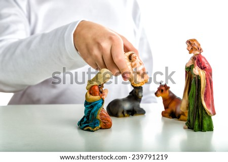 A boy put the statue of the Infant Jesus completing a simple Christmas Crib where the statues represent the Holy Family: the Virgin Mary, Saint Joseph and the infant Jesus, watched by ox and donkey - stock photo