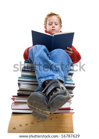 a boy reading on a stack of books