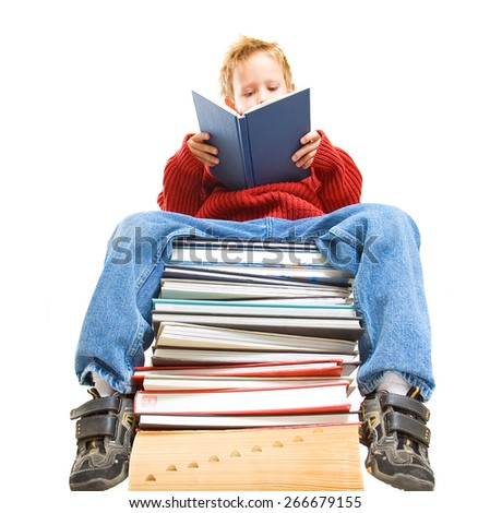 a boy reading on a stack of books - stock photo