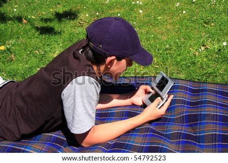A boy relaxing in the garden playing with his console game - stock photo
