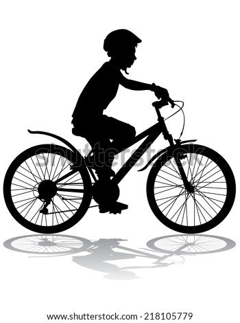 A boy rides a bicycle on a walk. - stock photo