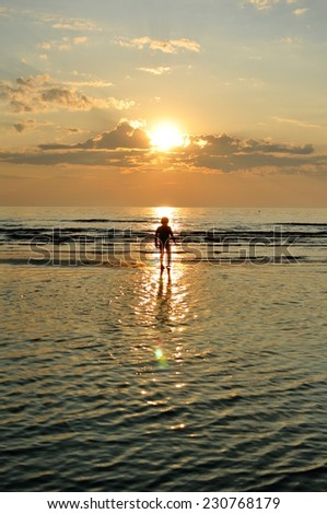 A boy running in the sea on sunset - stock photo