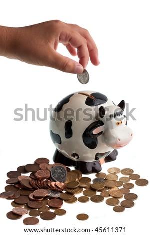 A boy's hand dropping a coin into a piggy bank - stock photo